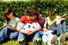 portrait of modern teens in casual clothes sitting on green grass and writing in - stock photo