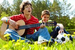 Portrait of happy lad playing the guitar with his friend near by Stock Photos