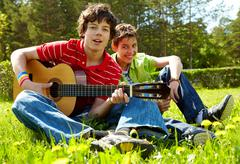 Portrait of happy lad playing the guitar with his friend laughing near by Stock Photos