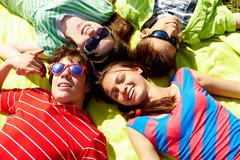 Above view of several happy teens lying head by head to each other Stock Photos