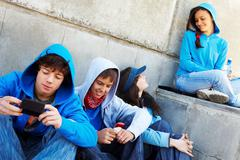 portrait of several teens spending time outdoors and interacting - stock photo