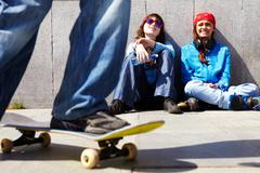 Stock Photo of two teen girls sitting on asphalt and watching their friend skateboarding outdoo