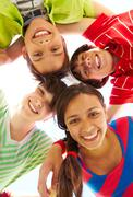 below view of several happy friends standing head by head to each other - stock photo