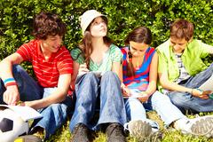 portrait of inspired teens sitting on green grass and writing in copybooks - stock photo