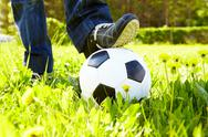 Horizontal image of soccer ball in green grass and shoes Stock Photos