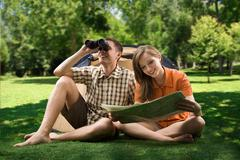 photo of resting couple sitting on green grass while girl reading paper and guy - stock photo