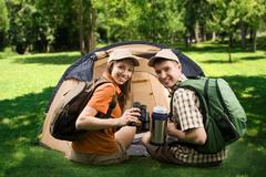 Photo of cheerful girl and guy sitting on green grass by tent and looking at cam Stock Photos