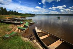 image of lake with some boats on the shore under cloudy sky - stock photo