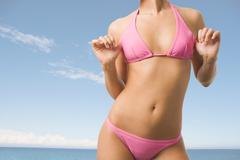 Image of luxurious woman torso in pink bikini on background of blue sky and sea Stock Photos