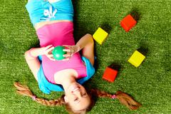 Above view of happy young girl lying on grass and having fun Stock Photos
