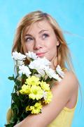 portrait of pretty girl with spring flowers on blue background - stock photo