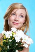 Portrait of pretty girl with bunch of chrysanthemums on blue background Stock Photos