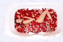portrait of young woman lying in the bathtub with red petals - stock photo