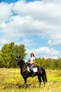 Stock Photo of image of happy female jockey sitting on black horse outdoors