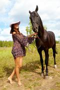 Image of smart female in hat and dress taking care of purebred horse outdoors Stock Photos