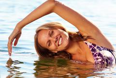 Portrait of fresh young girl doing stretching exercise in water at summer Stock Photos