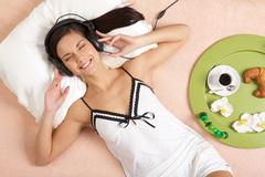 pretty girl listening to music in headphones and smiling while lying on bed - stock photo