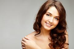 Stock Photo of portrait of feminine woman touching her shoulder and looking at camera