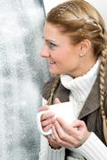 Amazed female with cup in hands looking through frosty window Stock Photos