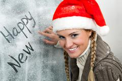 Happy female in santa cap looking at camera while writing on frosty window Stock Photos