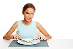 portrait of pretty young girl ready to eat peas and leeks - stock photo