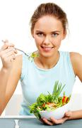 Portrait of pretty young girl with fork and bowl in hands eating vegetable salad Stock Photos
