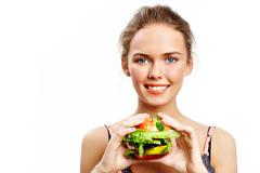 portrait of pretty young girl with vegetable burger in hands looking at camera - stock photo