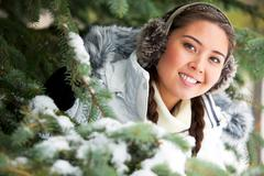 Portrait of beautiful woman looking out of firtree branches in forest Stock Photos