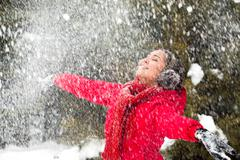 portrait of beautiful woman taking pleasure on snowy winter day - stock photo
