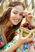 Portrait of pretty girl in country clothing holding cherries and looking at came Stock Photos