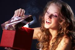 Image of happy girl looking into gift box and wondering Stock Photos