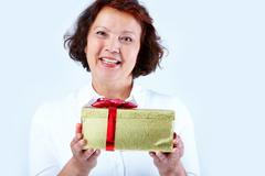 Portrait of middle-aged female looking at camera with smile and showing golden g Stock Photos