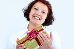 portrait of middle-aged female with golden giftbox laughing - stock photo