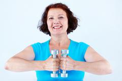 Portrait of middle-aged female doing physical exercise with dumbbells Stock Photos