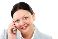 Friendly secretary speaking on the phone and looking at camera Stock Photos