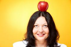 portrait of middle-aged female looking at red on her head - stock photo
