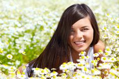 image of happy female peeking out of chamomile glade and smiling at camera - stock photo