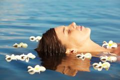 Close-up of peaceful female face above water surrounded by plumeria flowers Stock Photos