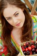 portrait of pretty girl with cherries looking at camera - stock photo