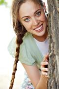 Image of happy female peeking out of tree trunk on summer day Stock Photos