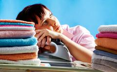 Portrait of young female between two stacks of colorful towels looking upwards Stock Photos