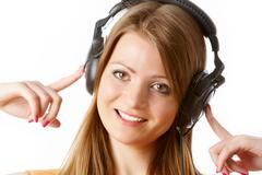 close-up of pretty girl touching headphones and looking at camera with positive - stock photo