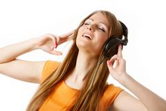 close-up of pretty girl in headphones listening to music with pleasure - stock photo