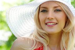pretty young lady in elegant hat smiling while looking at camera - stock photo