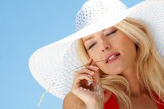 Pretty young lady in elegant hat enjoying summer against blue sky Stock Photos