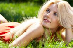 Photo of luxurious blonde lying in green grass in park Stock Photos