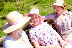 Portrait of three senior females sitting on bench at summer and chatting Stock Photos