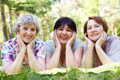 Portrait of three aged women resting on grass and looking at camera with smiles Stock Photos