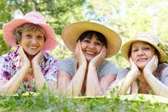 portrait of three aged women in elegant hats resting on grass - stock photo