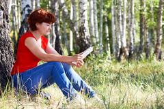 portrait of middle aged female reading book on grass in natural environment - stock photo